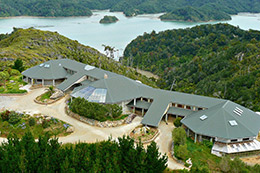photo of lodge from above and whanganui inlet behind